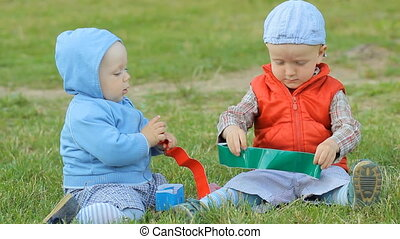 Two baby boys playing together on the lawn in the park