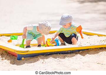 Two baby boys playing with sand