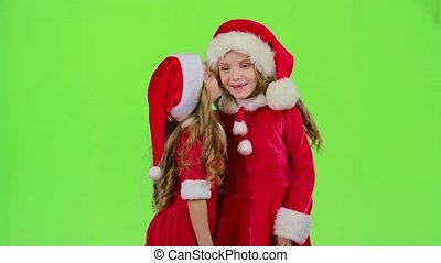 Two baby girls in New Year costumes tell each other secrets....