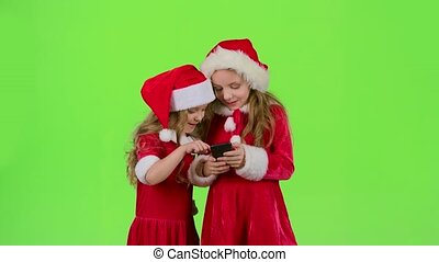 Two baby girls look at the pictures on the phone and laugh....