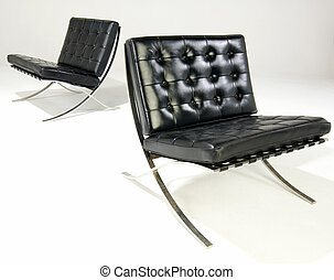 two bacelona chairs with black leather islaoted on white
