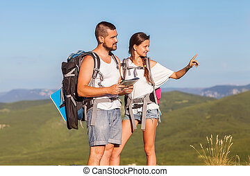 Two backpackers in mountains. Young couple examining the surroun
