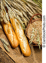 Two baguettes and a basket full of grain with ears