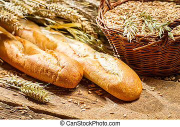Two baguettes and a basket of grain