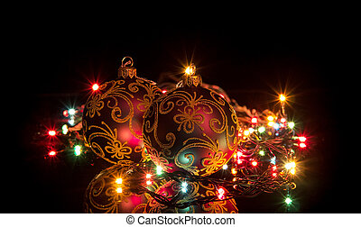 Two ball and a glowing garland on a dark