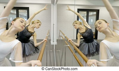 Two ballerinas are practiced by barre in ballet school.