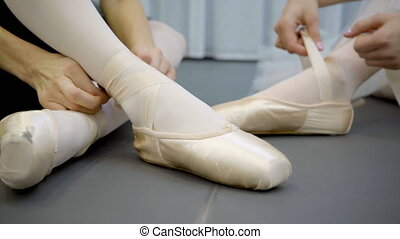 Two ballerinas are tying tape of pointe shoes sitting on...