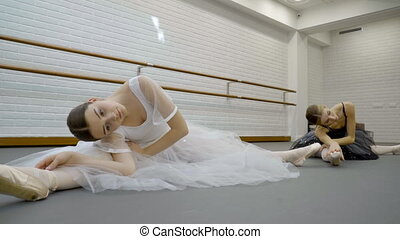 Two ballerinas do stretching in modern studio. Young women...