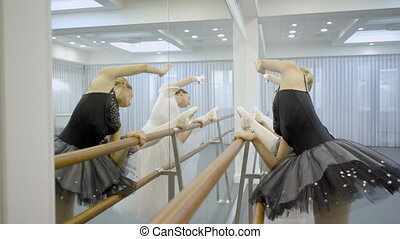 Two ballerinas in ballet tutu perform exercises at machine....