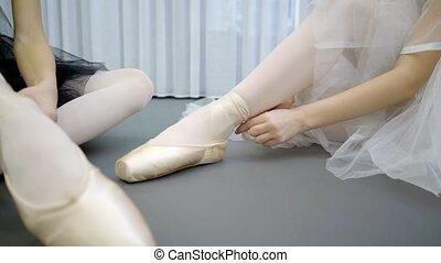 Two ballerinas tie pointe shoes on legs in ballet school....