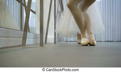 Two ballet dancers stand on their toes in ballet studio indoors.