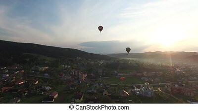 Two balloon flying over the city in the sun