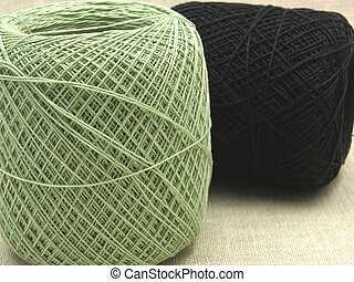 Two balls of wool lying and standing on a beige background