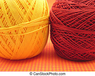 Two balls of wool on a checked background