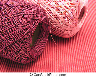 Two balls of wool on a red background