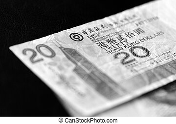 Two banknotes of twenty Hong Kong dollars on a dark background close-up. Black and white