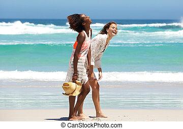 Two barefoot friends enjoying the beach lifestyle