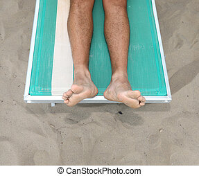 two barefoot of a boy on the deck chair