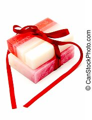 Two bars of soap tied with a red ribbon surrounded by white...