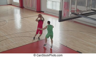 Two athletic african american basketball players playing one on one game on indoor basketball court. Handsome athlete performing jump shot over opposing defender in basketball game.