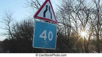 two battered road signs on one column.