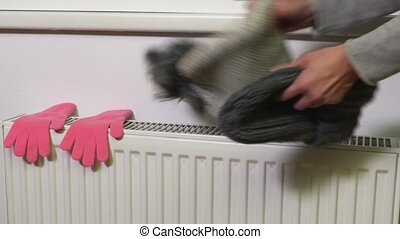 Two beanies and gloves on the heating radiator
