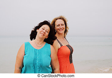 two beautiful 35 years old women standing on the beach