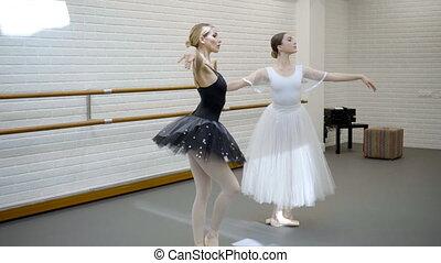 Two beautiful ballerinas rehearse dance in ballet studio....