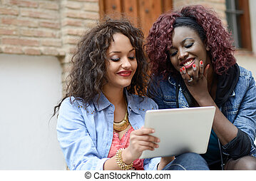 Two beautiful black girls with tablet computer in urban backgrund