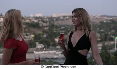 Two beautiful blondes in dresses drinking champagne by the glasses at the restaurant