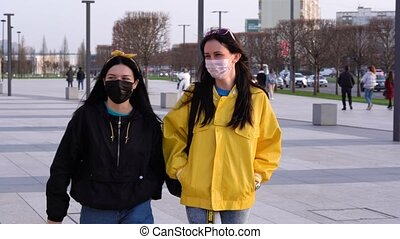 Two beautiful caucasian girls in black and yellow jackets walk around the street in medical protective face masks, talking, laughing, smiling against background of city, passers-by. Cars drive by.