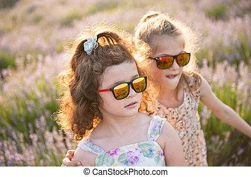 two beautiful caucasian little girls in trendy sunglasses summer flower field