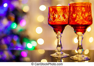 two beautiful crystal glasses on the background of the Christmas tree
