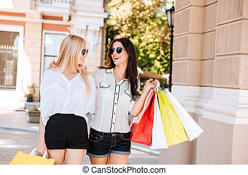 Two beautiful fashion models posing outside with shopping ...