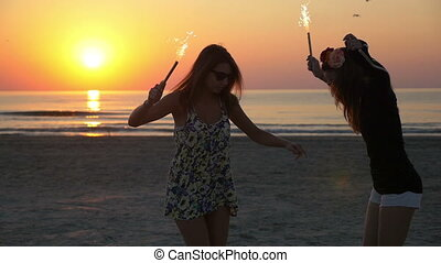 Two beautiful female teenagers on the beach with firework candles in their hands at sunrise