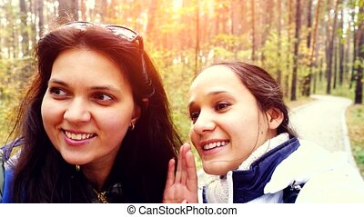 Two beautiful friends with cell phone camera taking photos selfie in autumn fall park. 3840x2160