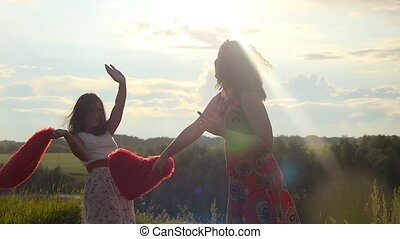 Two beautiful girl friends pillow fight on nature in sunset time