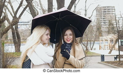 Two beautiful girlfriends blonde and brunette - talking standing under an umbrella. Sunny day, the wind blows.