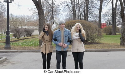 Two beautiful girls and a young man are walking along the street. Blonde and brunette talking on the phone, the guy does not like it.