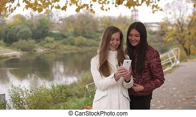 Two beautiful girls are walking in autumn park, watching a photo on the phone