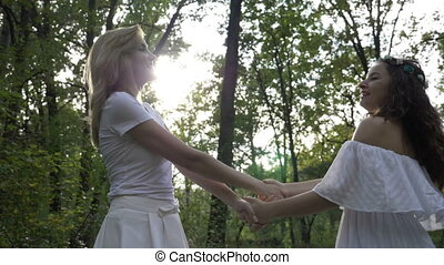 Two beautiful girls dressed in white angelic dresses dance in the green forest