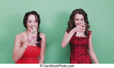Two beautiful girls drinking champagne