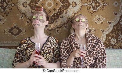 Two beautiful girls have fun together make fresh face masks...