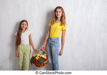 Two beautiful girls holding a basket of ripe vegetables