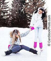 girls ice skating - two beautiful girls ice skating outdoor...