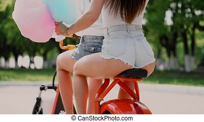 Two beautiful girls in denim shorts ride in the Park on an...