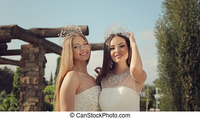 Two beautiful girls in elegant white dresses embroidered with stones in the crowns on their head posing in a park on nature
