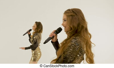 Two beautiful girls in shiny dresses dancing and singing in the studio on a white background.
