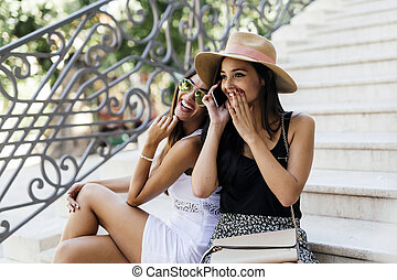 Two beautiful girls laughing while talking on phone