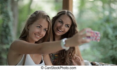 Two beautiful girls making selfie in the forest